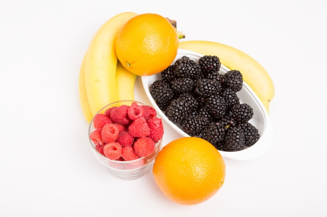 Oranges Raspberries Blackberries And Bananas On White